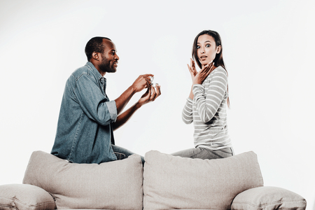 Shocked woman looking at camera while her lover making marriage proposal. Isolated on background Stock Photo