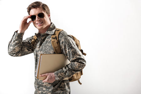 Joyful young male officer going and setting straight his spectacles. He is smiling and holding document case. Isolated on background. Copy space in right side