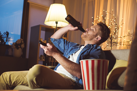 Side view interested unshaven male drinking alcohol while typing in remote controller in apartment. Leisure concept