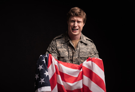 Portrait of upset male soldier screaming despairingly. He is looking at camera and holding flag in hands. Isolated on background