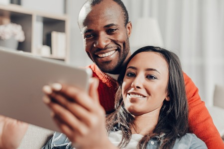 Portrait of two amorous person spending time with device at home. Their faces expressing enjoyment Stock Photo