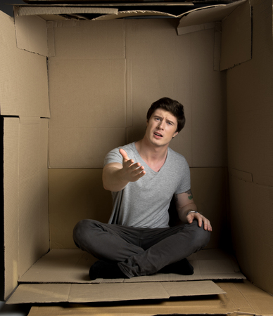 Full length portrait of young frustrated man is sitting in cardboard box while looking at camera indignantly and gesticulating while feeling discomfort.