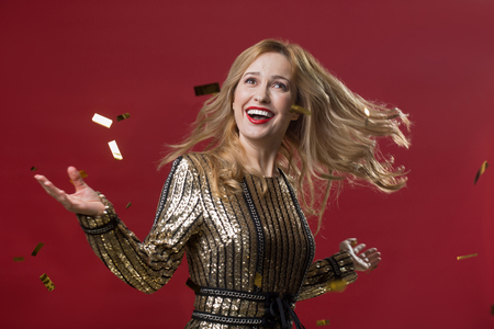 Waist up portrait of triumphant woman getting pleasure from holiday celebration. Isolated on red background Stock Photo