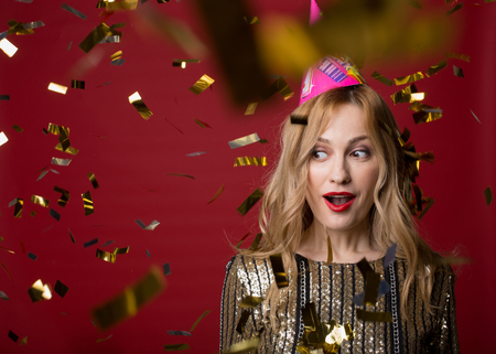 Portrait of surprised female in cone cap standing surrounded by sparkling confetti and looking aside with opened mouth. Stock Photo