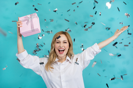 Portrait of joyful good looking lady raising her hands up and holding present. Confetti flying around. Isolated on blue background 写真素材
