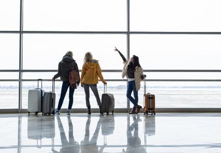 出発ゲート付近で搭乗を待つ穏やかな女の子たち。彼らは窓から飛行機を観察している。右側のスペースをコピーする