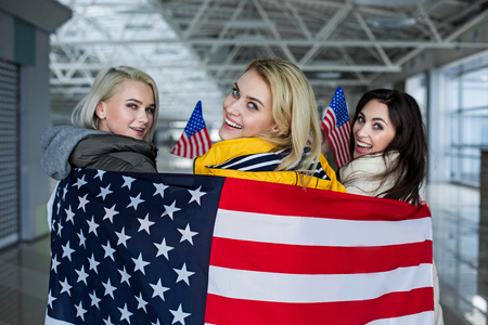 Patriotism concept. Enjoyed group of girls going abroad. They are posing wrapped in national colors of usa