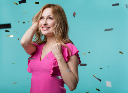 Portrait of glad attractive woman standing surrounded by confetti and looking ahead with happy smile.