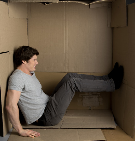 Full length of young man is sitting in cardboard box while pushing the wall with his feet and trying to move them. 스톡 콘텐츠