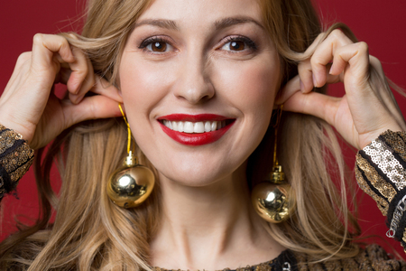 Close up of female face wearing christmas tree decorations on ears and smiling. Isolated on red background