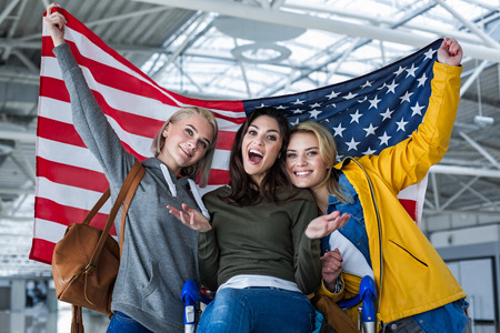 Portrait of three happy female friends standing at the airport.