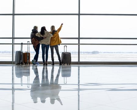 ターミナルの滑走路をじっと見つめている女の子たち。彼らは背中を抱きしめて立っている。右側のスペースをコピーする