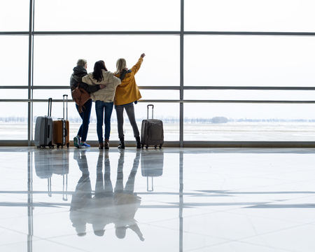 Girls staring at runway in the terminal. They are standing with their backs and hugging. Copy space in right side
