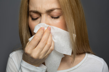 Contagious disease. Cheerless lady covering her nose with tissue and sneezing. Isolated on background