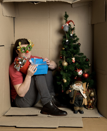 Happy young man is celebrating new year alone inside small cardboard box with decorated spruce and bright gifts. Stock fotó
