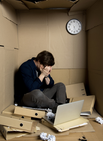 Full length of tearful employee is sitting with laptop inside his cramped carton office while hiding his face in his hands. Stock Photo