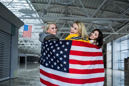 空港ホールに立っている3人の女友達。
