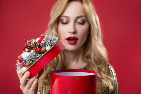 Portrait of serene female person opening box with present. Focus on case. Isolated on red background