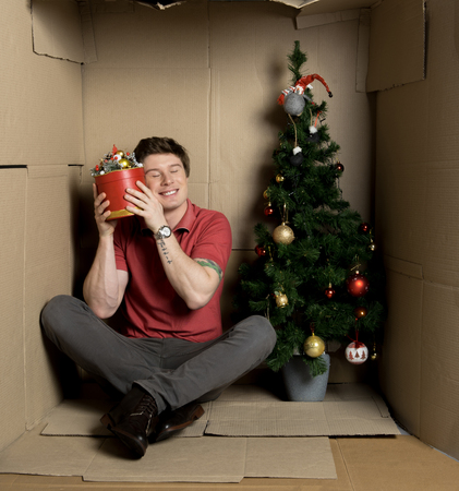 Full length portrait of cheerful guy is sitting on floor inside cramped cardboard room with christmas-tree.