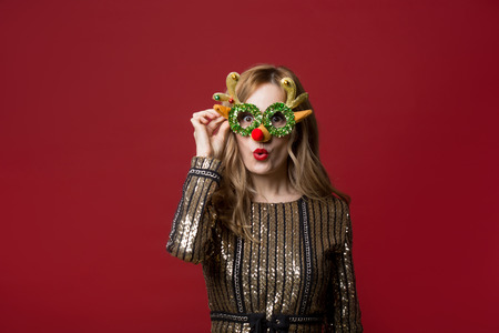 Portrait of jolly female in sparkling clothes holding funny reindeer eyeglasses. Isolated on red background Foto de archivo