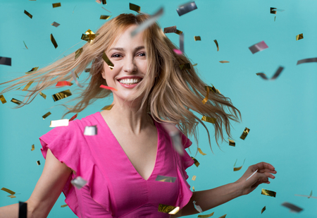 Portrait of young woman posing and laughing. Confetti is falling down. Isolated on blue background Stock Photo