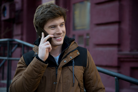 Cheerful young attractive man is talking on modern mobile phone while looking aside with wide smile.