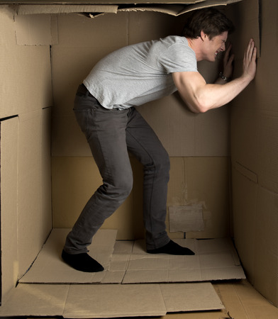 Full length of young man is standing in cardboard box and pushing wall with effort