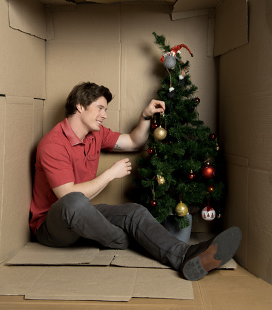 Full length of young man is sitting on floor inside small cardboard house with green tree.