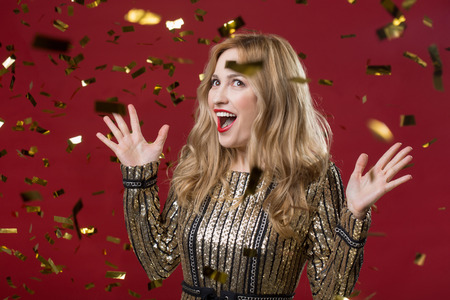 Waist up portrait of cheerful woman looking at confetti flying around her. Isolated on red background