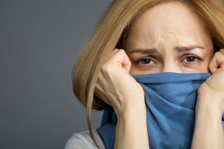 Depressed blonde lady covering her mouth with clothes and wrinkling her forehead expressing pain. Copy space in left side.
