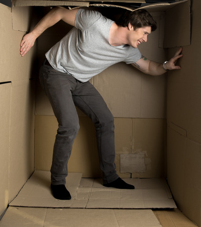 Full length of young irritated man is standing in cramped cardboard box and pressuring on walls while trying to expand them.
