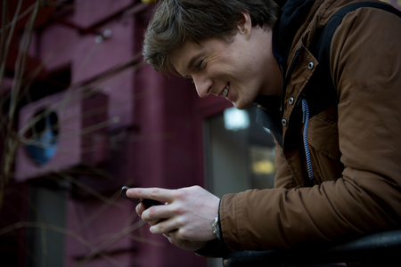 Profile of delighted young man is looking at screen of his mobile phone while sharing pleasant news. Stock Photo