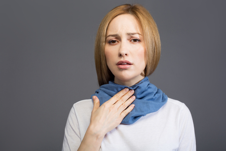 Portrait of ill blonde female touching her throat and looking at camera with sadness, her neck wrapped with scarf. Zdjęcie Seryjne - 95822418