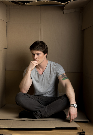 Full length of young man is sitting in carton box and looking aside thoughtfully while touching his chin. 스톡 콘텐츠