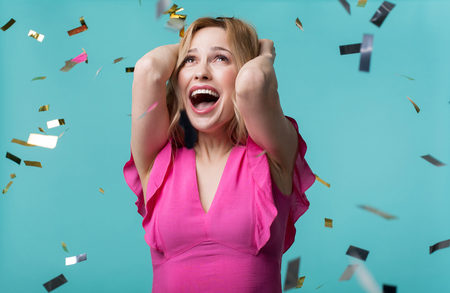 Portrait of excited beautiful woman in cute dress holding her hands on head while looking at golden confetti flying around.