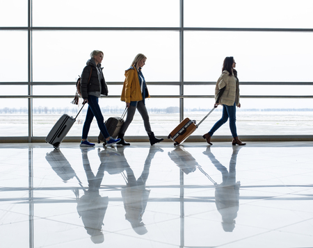 Side view profile of serene female tourist going flying. They are walking one after another and carrying suitcases. Copy space