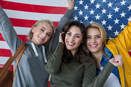 Nationalism concept. Portrait of excited women standing close. Banner of united states is on background
