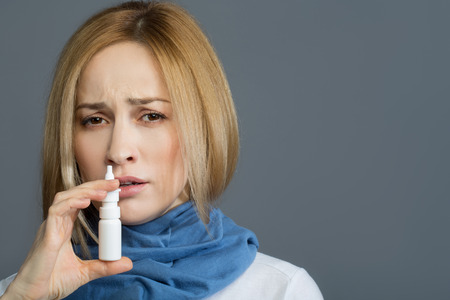 Portrait of sick joyless woman with scarf on her neck using nose spray. Isolated on background. Copy space in right side
