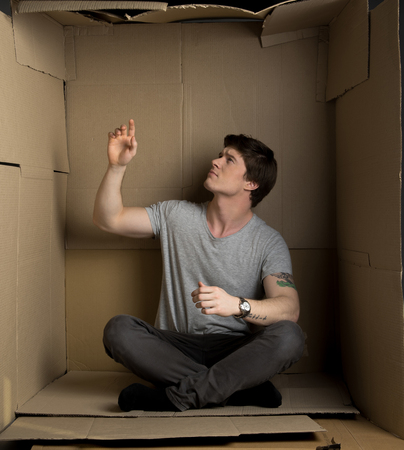 Full length of young man is sitting on floor of his cramped cardboard box.