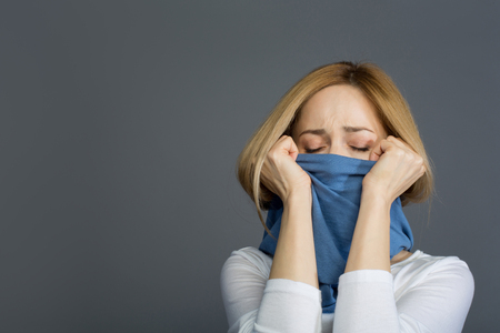 Unhappy lady standing with eyes closed and covering her mouth with scarf, her face expressing pain.