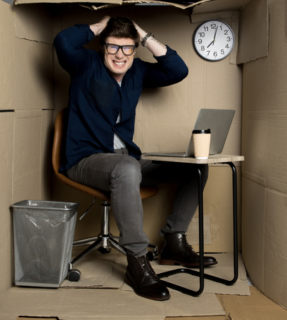 Full length portrait of exasperated manager is sitting at table in cramped cardboard office and screaming while looking at camera with anger.