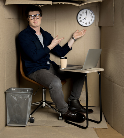 Full length portrait of unhappy young manager is sitting at table in cramped cardboard office and pointing on clock. Stock Photo