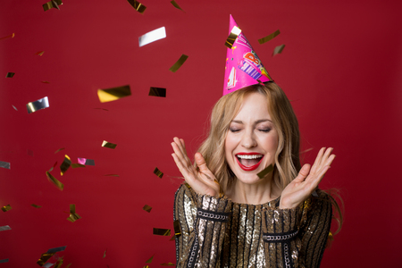 Portrait of glad young woman in cone cap standing with eyes closed in cloud of golden confetti and laughing. Stock Photo