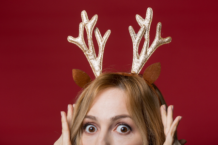 Close up of female head wearing golden reindeer antlers headband, looking amazed. Isolated on red background
