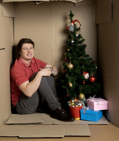 Full length portrait of optimistic young man is sitting on floor inside confined cardboard room with christmas-tree and gifts.