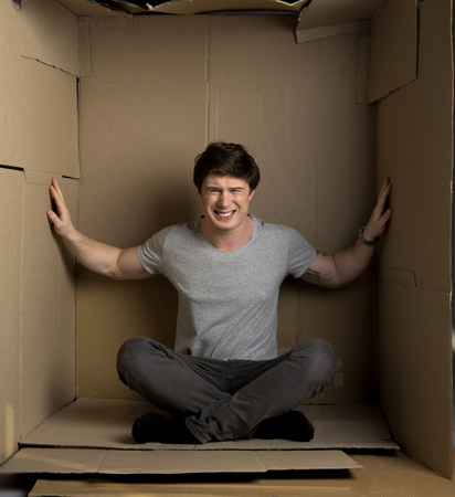 Full length portrait of young depressed man is sitting in cardboard box. He is pressuring on walls while trying to extend them 版權商用圖片
