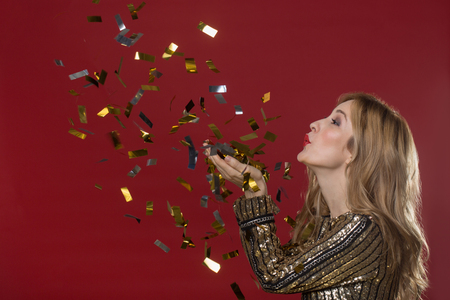 Side view profile of playful lady standing and blowing at confetti. Isolated
