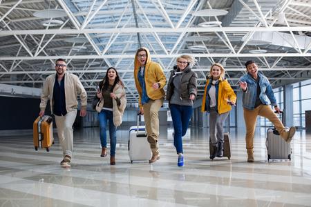 Pełnometrażowy portret grupy turystów ścigających się na lotnisku. Ich twarze są radosne