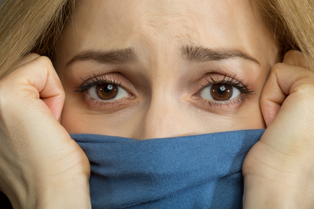 Close up of female face half covered with clothes. Woman is looking at camera with sadness Stock Photo