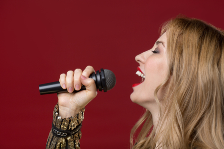 Side view profile of peaceful lady holding mike and singing with eyes closed. Isolated on red background Stock Photo